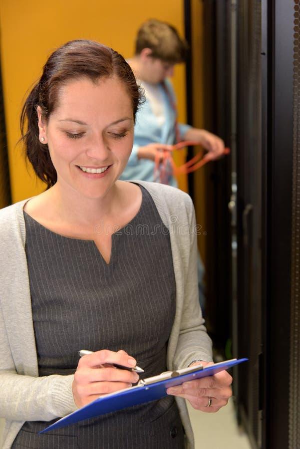 Kvinnatekniker som arbetar i datacenter royaltyfria foton