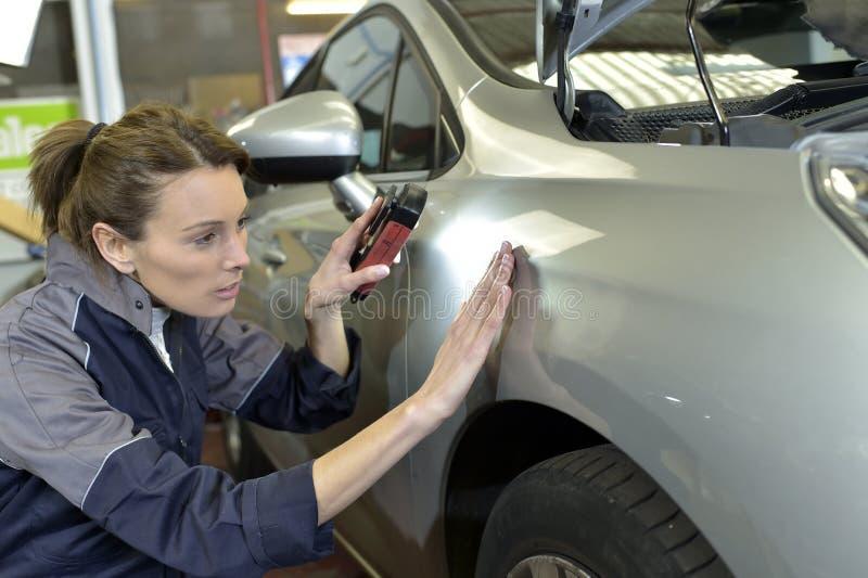 Kvinnateknikeren som arbetar i en bil, shoppar arkivfoto