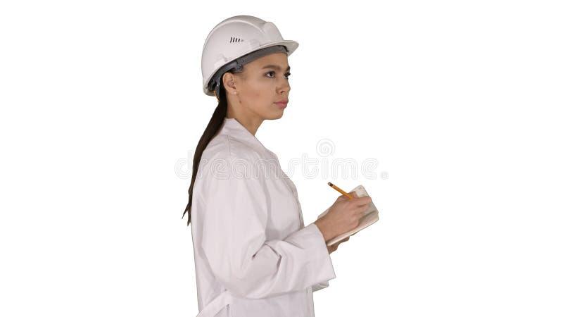 Kvinnateknikern med hjälmen är den rymmande pennan och kontrollistan som ner sätter något, medan gå på vit bakgrund royaltyfri fotografi