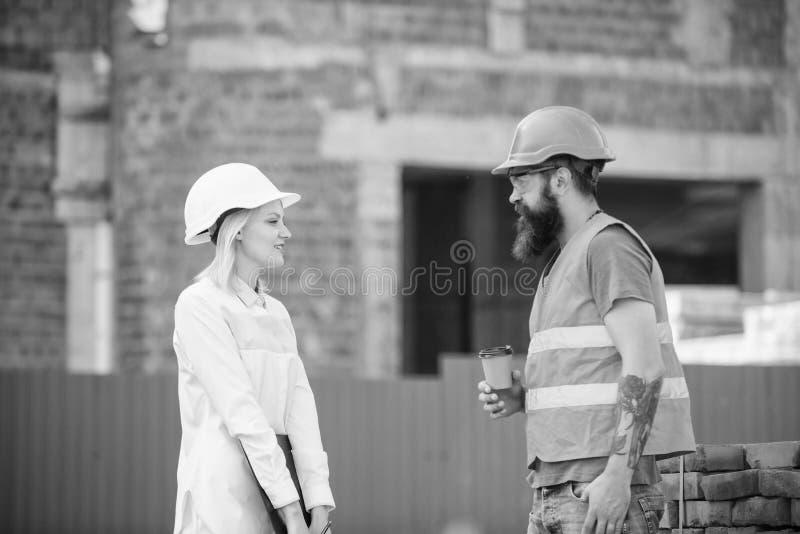 Kvinnateknikern och den brutala byggm?staren meddelar bakgrund f?r konstruktionsplatsen Begrepp f?r konstruktionslagkommunikation royaltyfri bild