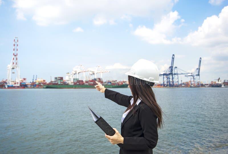 Kvinnateknikern som arbetar med behållarelastfrakter, sänder i skeppsvarv på skymning för logistisk import royaltyfria bilder