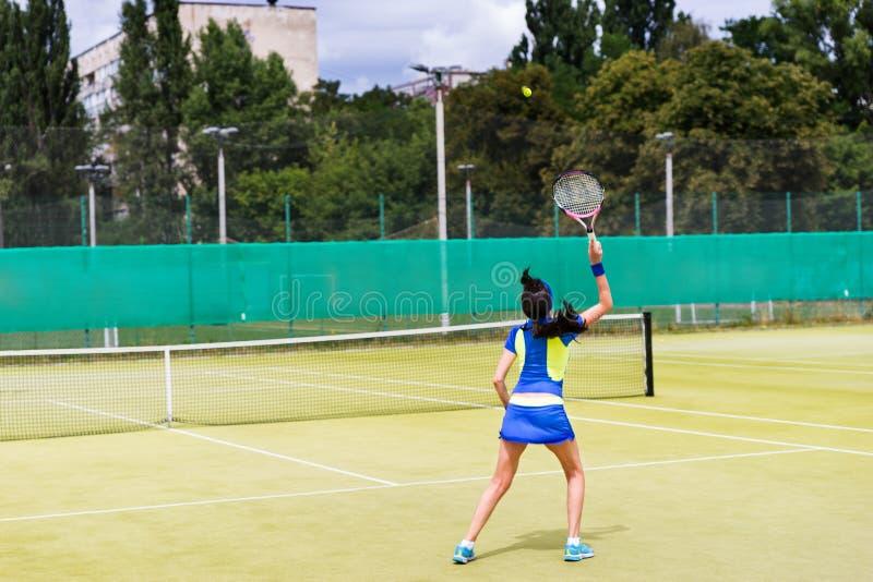 Kvinnatennisspelare i handling på en utomhus- domstol arkivfoto
