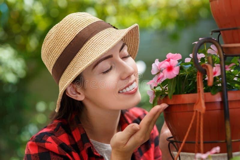 Kvinnaträdgårdsmästare som luktar blommor royaltyfria foton