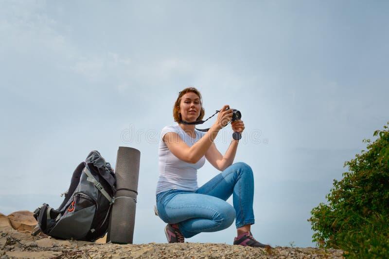 Kvinnaturist avgjord f?r att koppla av och ta n?gra minnesv?rda foto p? telefonen Sky p? bakgrunden arkivbild