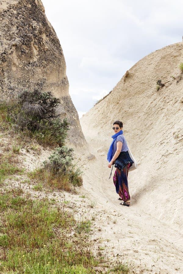 Kvinnaturist i dalen av Cappadocia Gå i de sandiga bergen royaltyfri foto