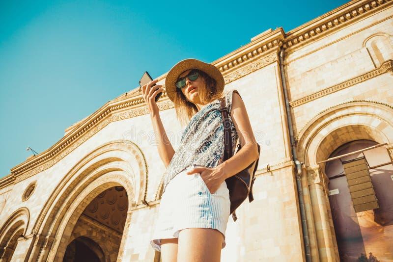 Kvinnaturist i hatt med ryggsäcken genom att använda gps-navigering på mobiltelefonen Sommarmodestil Staden turnerar Undersök vär royaltyfria foton