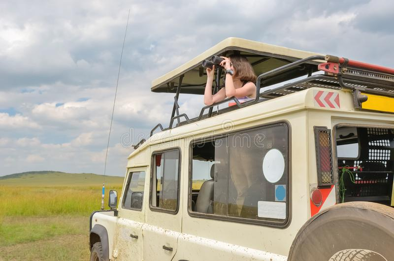 Kvinnaturist på safari i Afrika, lopp i Kenya, hållande ögonen på djurliv i savann med kikare royaltyfri foto