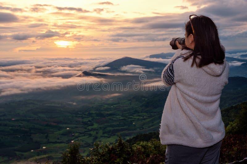 Kvinnaturisten använder en DSLR-kamera som fotograferar naturlandskap soldimmaberget i vintern under soluppgång på höjdpunkt royaltyfri fotografi