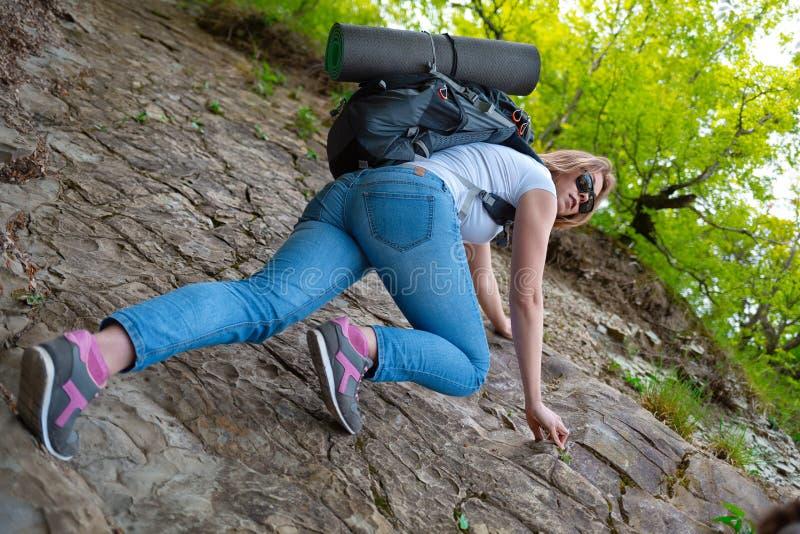Kvinnaturisten kl?ttrar vaggar Turism och fotvandra Botten besk?dar royaltyfria foton