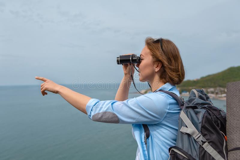 Kvinnaturisten ser till och med kikare och punkter till något med hans hand Bl? himmel och hav i bakgrunden fotografering för bildbyråer