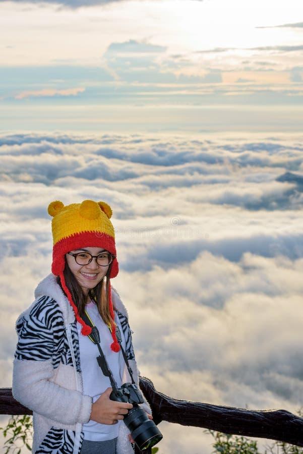 Kvinnaturisten som rymmer en DSLR-kamera på härligt naturlandskap av dimma, är som havet i vintern under soluppgångbakgrund arkivfoto