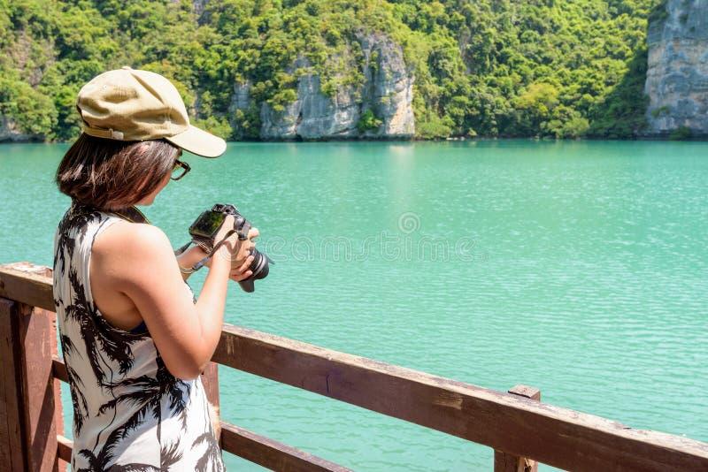Kvinnaturisten som tar foto, slösar lagun royaltyfri bild