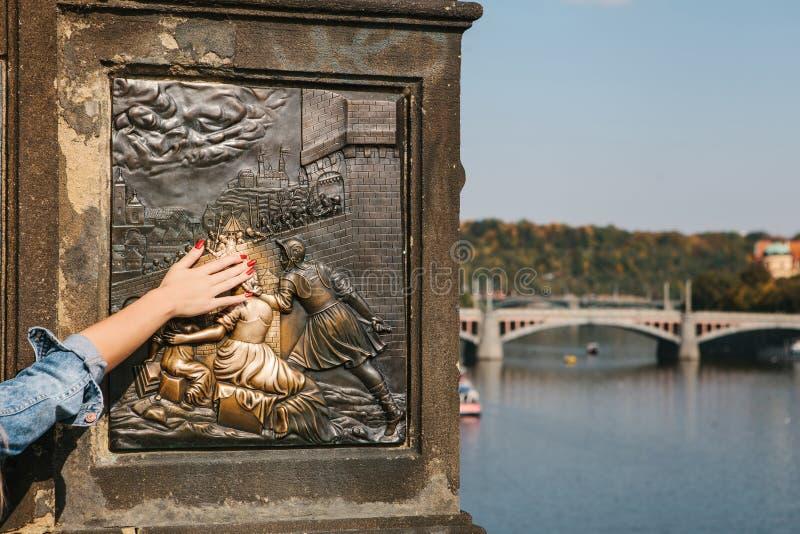 Kvinnaturisten trycker på en bronsstaty av John av Nepomuk på den Charles bron i Prague, Tjeckien för bra lycka arkivfoto