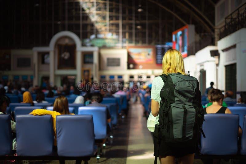 kvinnaturister och ryggsäck som väntar hennes vän på den Bangkok järnvägsstationen Thailand arkivbilder