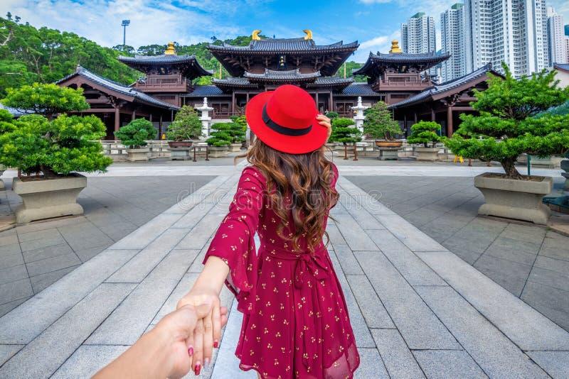 Kvinnaturister som rymmer mans hand och leder honom till den ChiLin Nunnery templet, Hong Kong royaltyfri bild
