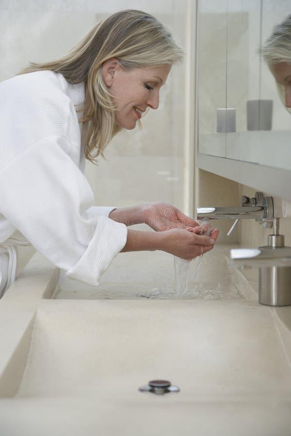 Kvinnatvagningframsida i badrumvask royaltyfri bild
