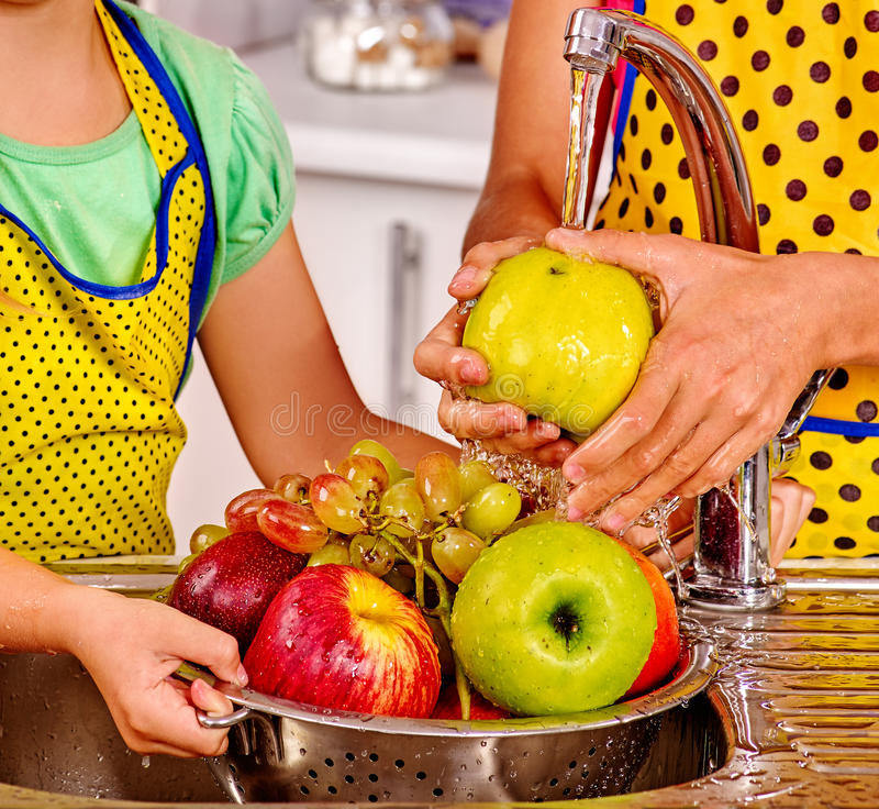Kvinnatvagningfrukt på kök royaltyfri bild