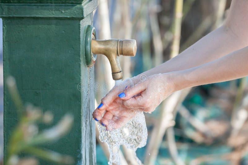 Kvinnatvagninghänder i stadsspringbrunn royaltyfri foto