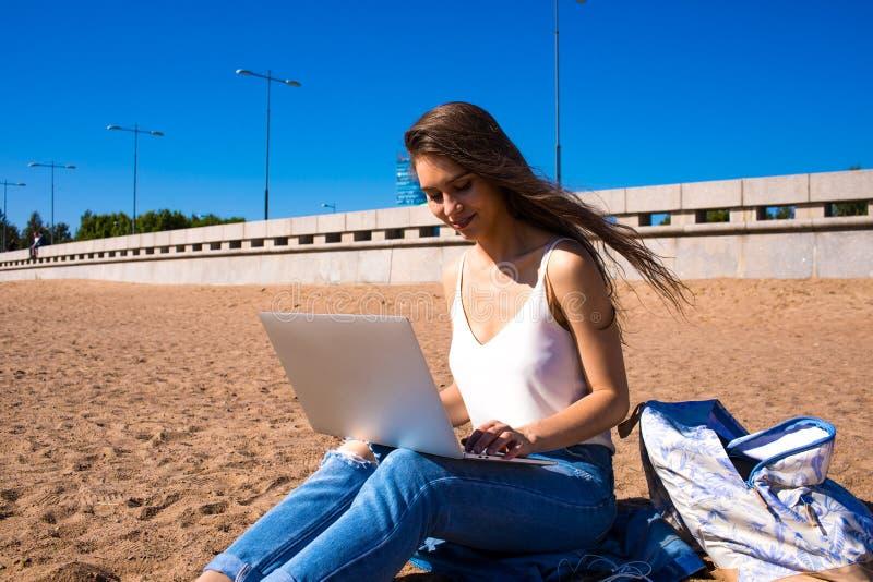 Kvinnauniversitetsstudent som lär direktanslutet på netbook som vilar på kustlinjen royaltyfri bild