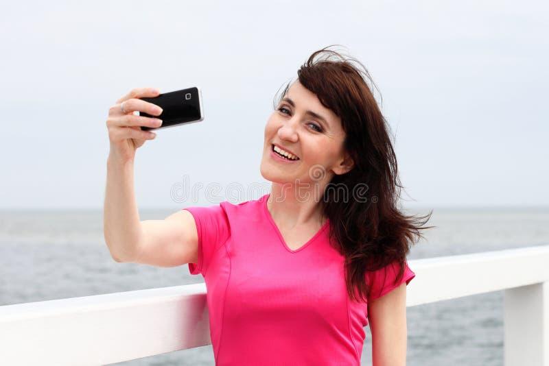 Kvinnauppvisningsskärm av den mobila telefonen royaltyfri fotografi