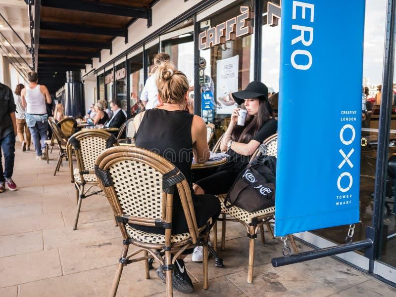 Kvinnavänner sitter på hamnplats för tornet för den Caffe Nero tabellyttersidan Oxo, S royaltyfria foton