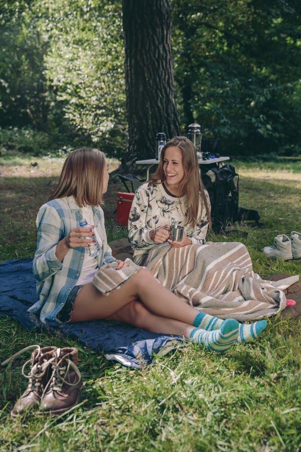 Kvinnavänner som skrattar sammanträde i campingplatsen fotografering för bildbyråer