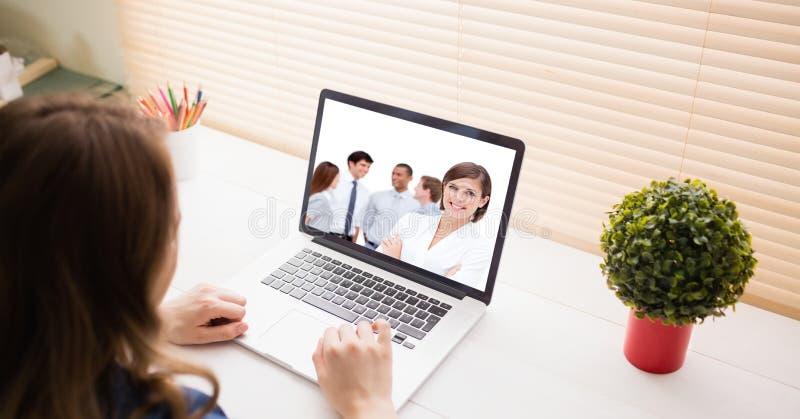 Kvinnavideoconferencing med kollegor på bärbara datorn arkivbild