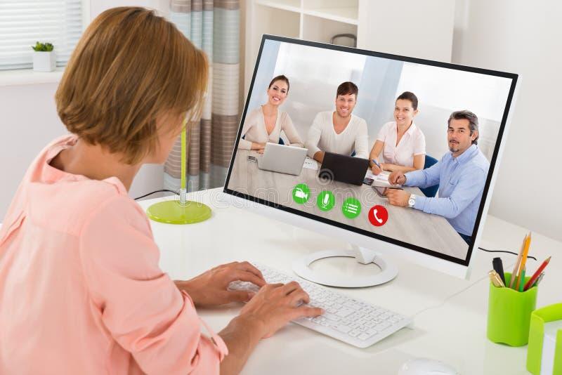 KvinnaVideoconferencing på datoren arkivbild