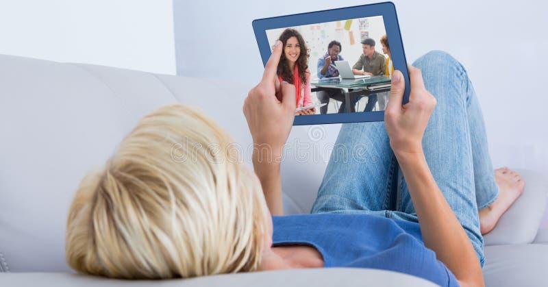 Kvinnavideoconferencing på minnestavlaPC, medan ligga på soffan royaltyfria foton