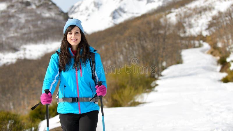 Kvinnavinter som fotvandrar i snöig spår arkivbild