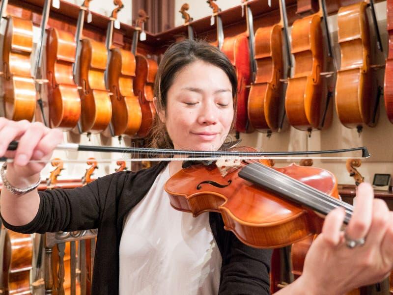 Kvinnaviolinist Playing en fiol i en Music Store arkivbilder