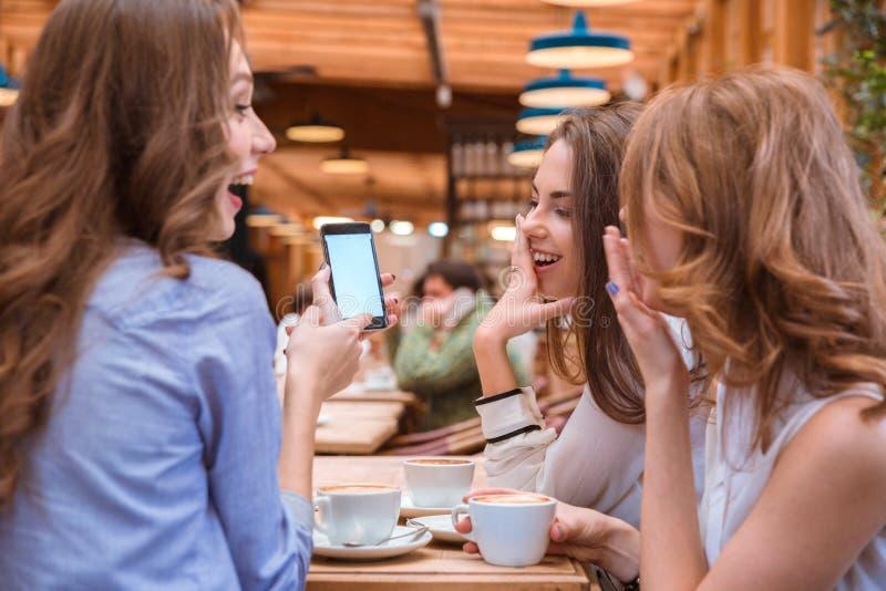 Kvinnavisning något på smartphoneskärmen till hennes flickvänner arkivbilder
