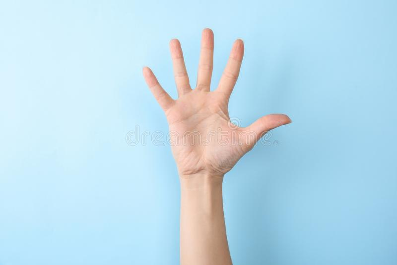 Kvinnavisning nummer fem på färgbakgrund Teckenspråk arkivfoton