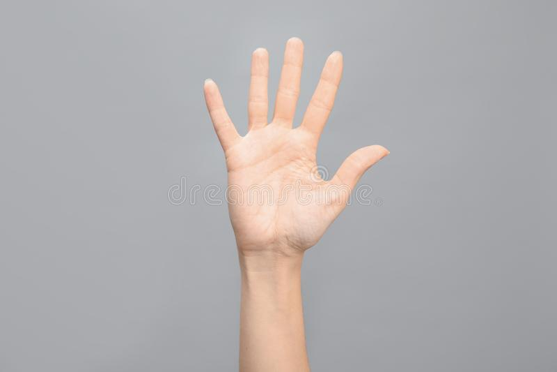Kvinnavisning nummer fem på grå bakgrund Teckenspråk royaltyfri bild