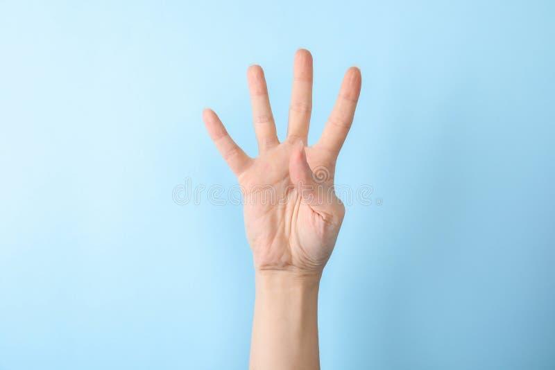 Kvinnavisning nummer fyra på färgbakgrund Teckenspråk fotografering för bildbyråer