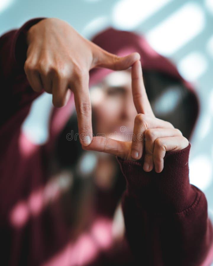 Kvinnavisning som inramar handgest på ljus bakgrund royaltyfri foto