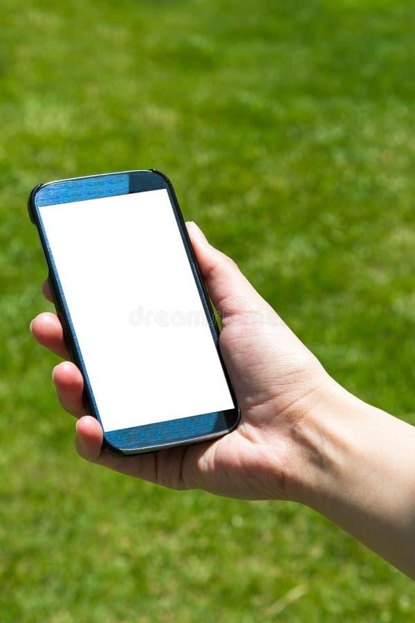 KvinnavisningSmart telefon på naturligt fotografering för bildbyråer