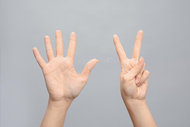 Kvinnavisningtecken sju på grå bakgrund Kroppsspråk arkivfoto