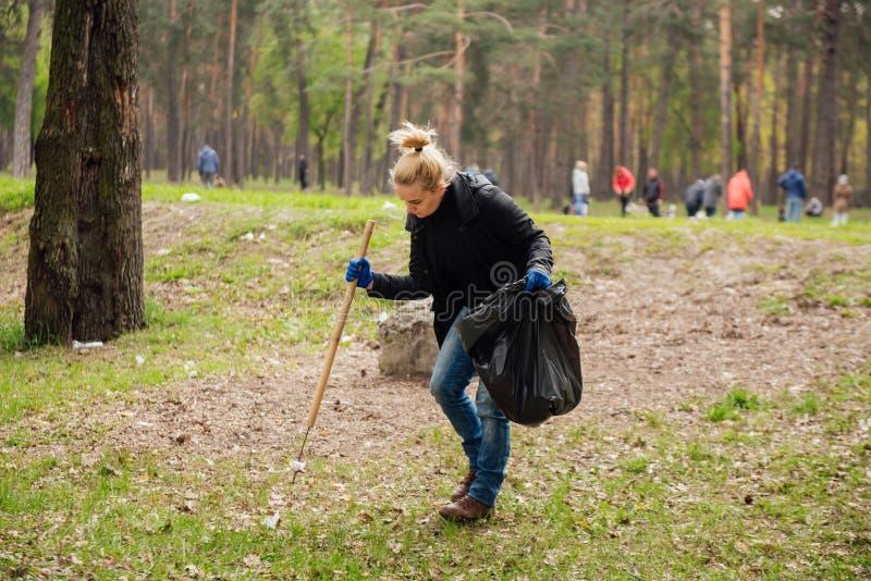 Kvinnavolontären som samlar avskräde parkerar in arkivfoto