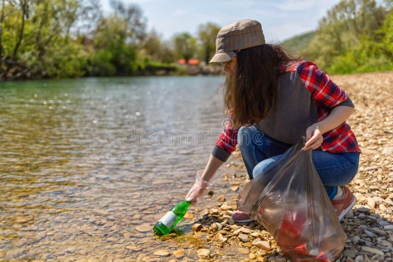 Kvinnavolontärhjälp att göra ren kusten av floden av avskräde Jorddag och milj?- f?rb?ttringsbegrepp eco arkivfoto