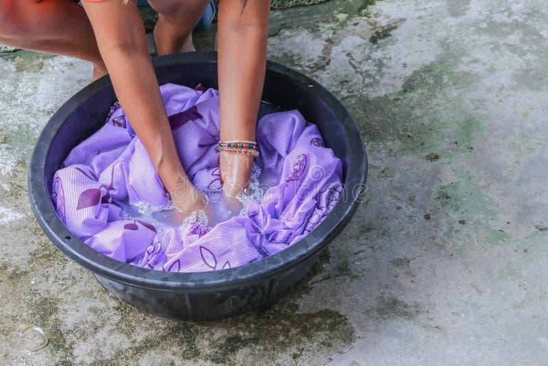 Kvinnawashhänder smutsar ner kläder i handfatsvarten för att rentvå royaltyfria bilder