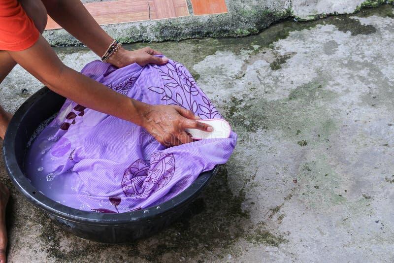 Kvinnawashhänder smutsar ner kläder i handfatsvarten för att rentvå arkivfoto