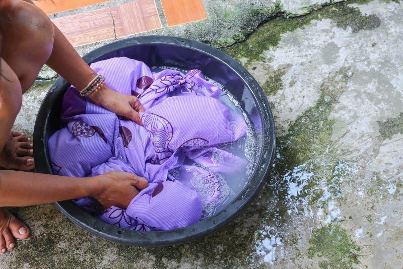 Kvinnawashhänder smutsar ner kläder i handfatsvarten för att rentvå royaltyfria foton