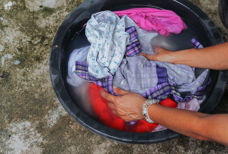 Kvinnawashhänder som smutsig kläder i handfatet svärtar för, rentvår royaltyfria bilder