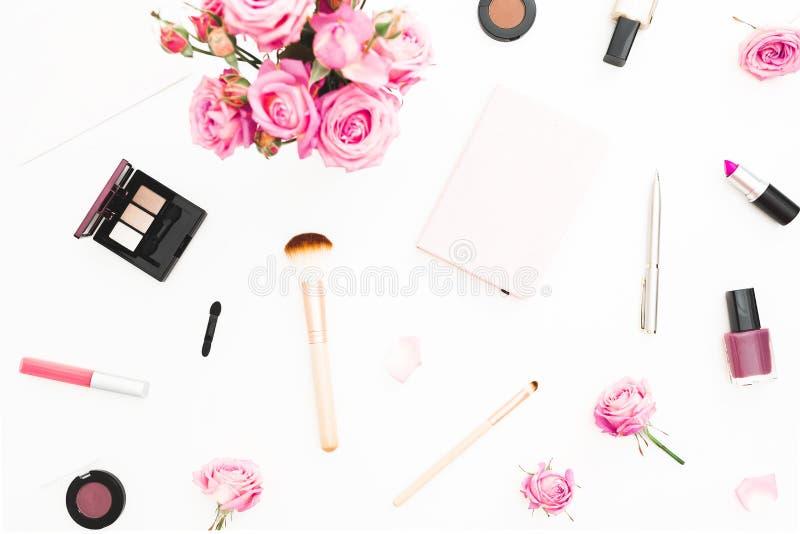 Kvinnaworkspace med den rosa rosbuketten, skönhetsmedel, dagbok på vit bakgrund Top beskådar Lekmanna- hem- kvinnligt skrivbord f royaltyfri fotografi