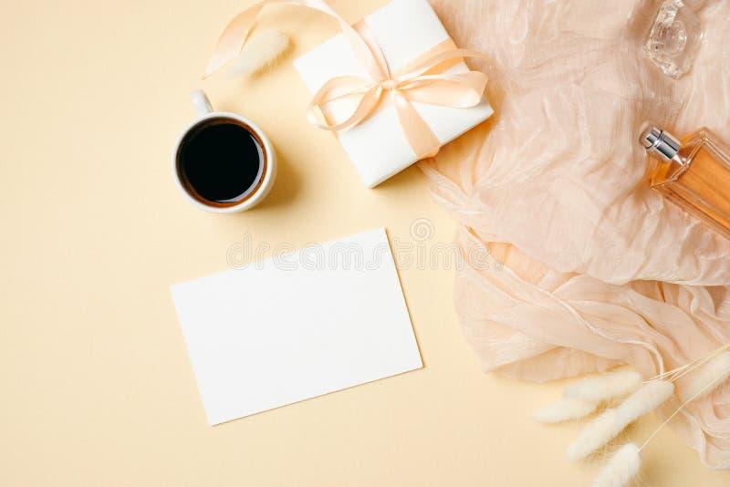 Kvinnaworkspace med papperskortet, kaffekoppen, gåvaasken och doftflaskan på beige bakgrund Kvinnligt skrivbord br?llop f?r roman arkivbild