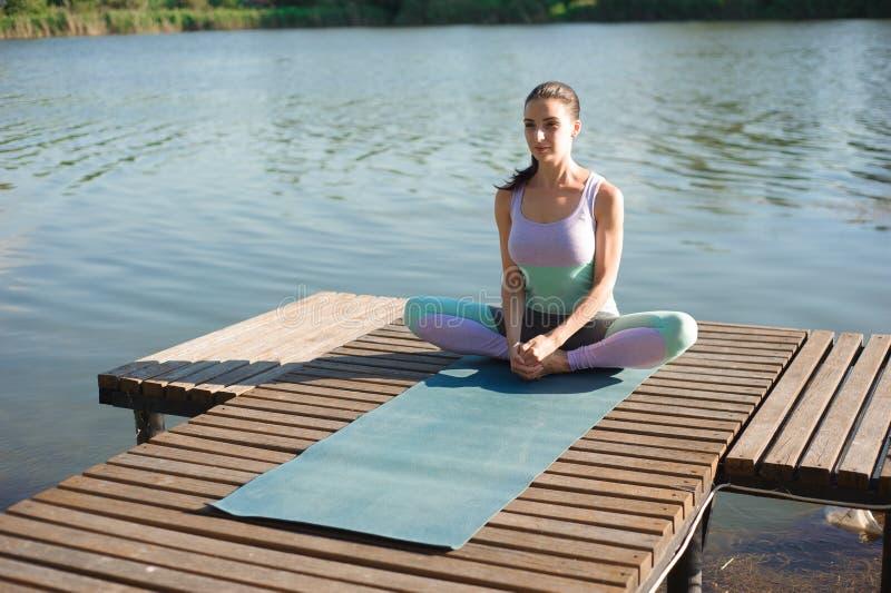 Kvinnayoga - koppla av i natur Caucasian kvinnayoga på bron som mediterar i yoga, poserar på en bergström arkivfoton