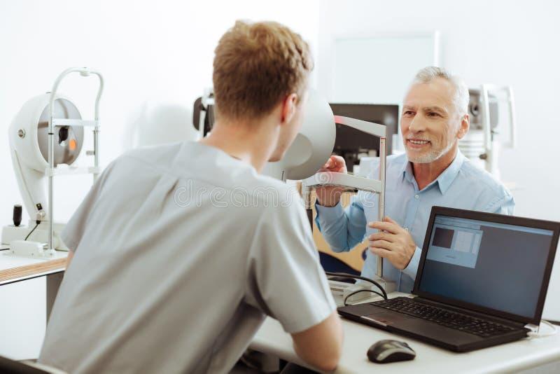 Kvinnlig ögonspecialist som sitter nära bärbara datorn som talar till hennes patient fotografering för bildbyråer