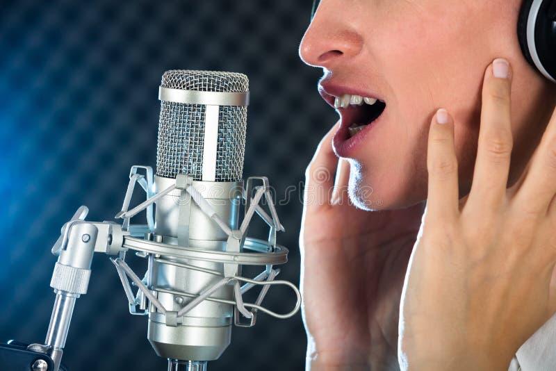 Kvinnlig öppen mun för ` s med röd läppstift i Front Of Microphone arkivfoto