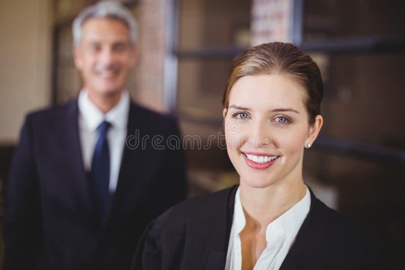 Kvinnlig advokat som ler medan manlig kollega i bakgrund royaltyfri foto